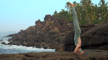 flat head : slim athletic woman does head stand on flat stone near rolling ocean waves and palm trees low angle shot extreme slow motion. Concept fitness sports yoga healthy lifestyle