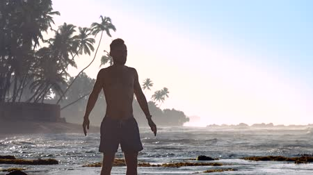 meditál : muscular sportsman meditates against ocean waves and palms silhouettes in morning extreme slow motion. Concept yoga and healthy lifestyle