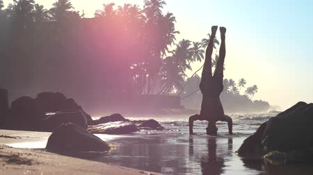 silhouette of palm : muscular athlete stands on hands and head in shallow ocean water in sunny summer morning slow motion. Concept fitness and healthy lifestyle