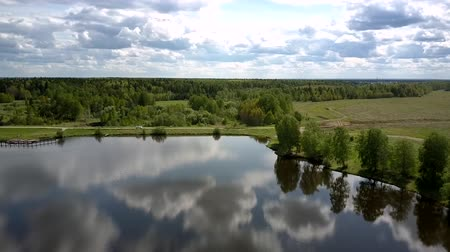 silvicultura : river reflects white clouds and green trees silhouettes near dense forest and field with ground road aerial view. Concept nature conservation and environmental change