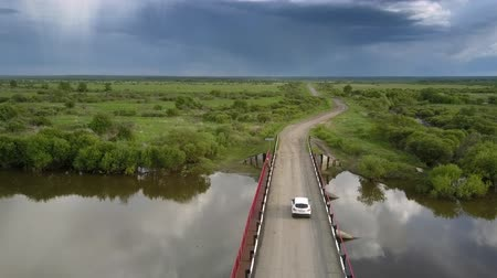 utilidade : white car drives along bridge over calm river reflecting trees and clouds silhouettes pictorial aerial view. Concept unspoiled nature and countryside