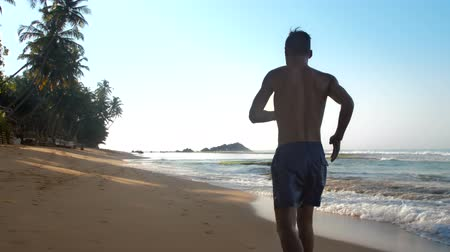 bum : strong athlete runs along yellow sandy beach between endless ocean and green palms slow motion backside view. Concept healthy lifestyle Stock Footage