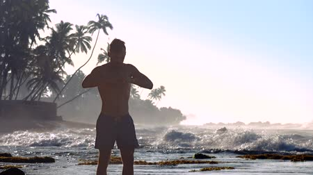 meditál : handsome man meditates on ocean coast against foaming waves and palms silhouettes slow motion. Concept meditation and teacher