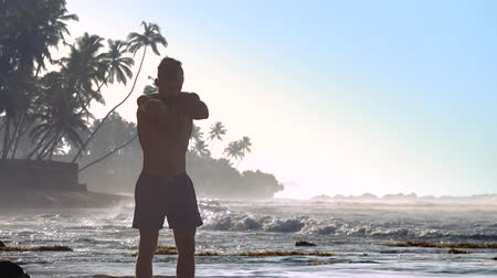 ginástico : strong sportsman stands in meditation pose against foaming ocean waves and palms silhouettes extreme slow motion. Concept yoga and guru
