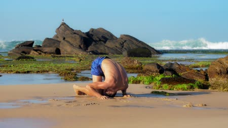 meditál : muscular sportsman meditates in yoga pose on wet sand against brown cliff and endless ocean extreme slow motion. Concept fitness and wellness lifestyle