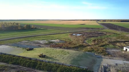 yem : wonderful aerial view modern ensilage harvesters tamp silo pit near farm against clear blue sky Stok Video