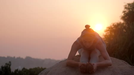 chakra : woman yoga practitioner in grey tracksuit does exercise on old rock against orange tropical sunrise low angle shot slow motion. Concept fitness sports yoga healthy lifestyle