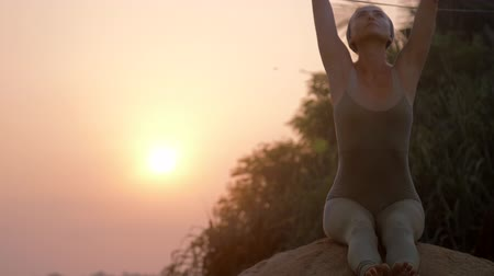hatha : relaxed girl raises hands and bends over doing fitness on large stone at tropical sunrise low angle shot slow motion. Concept fitness sports yoga healthy lifestyle