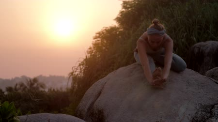 колено : slim woman with hair bun practices yoga on huge old rocks against red morning sunlight low angle shot slow motion. Concept fitness yoga healthy lifestyle Стоковые видеозаписи