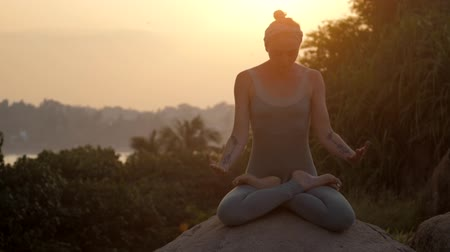 низкий : slim girl with tattoos on arms sits in padmasana on large round rock against pictorial sunrise low angle shot slow motion. Concept fitness yoga wellness lifestyle