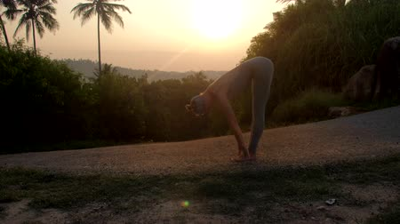 saudação : young flexible woman stands in uttasana doing sun salutation complex in tropical park with palms at sunrise slow motion Concept fitness yoga wellness lifestyle Vídeos