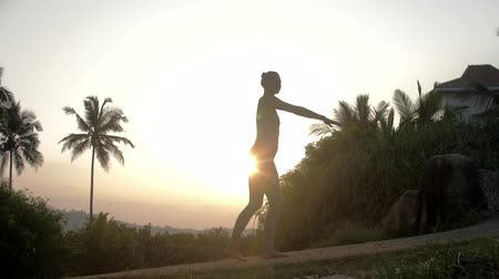 pilates : young slim lady silhouette doing yoga exercises on track against exotic plants and house at pictorial sunrise low angle shot slow motion. Concept fitness yoga wellness lifestyle