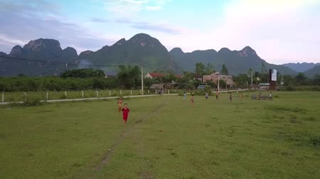 cercar : PHONG NHAVIETNAM - MAY 10 2018: Children play football using gate made from sticks on green grass field surrounded by mountain range aerial view on May 10 in Phong nha Stock Footage
