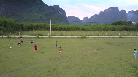 вратарь : PHONG NHAVIETNAM - MAY 10 2018: Active children play football on field near motorcyclist driving along narrow road under gray sky aerial view on May 10 in Phong nha Стоковые видеозаписи