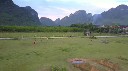 вратарь : PHONG NHAVIETNAM - MAY 10 2018: Children play football on green flat valley against vegetable gardens and high forestry mountain ranges aerial view on May 10 in Phong nha