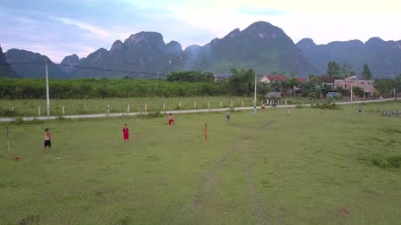 вратарь : PHONG NHAVIETNAM - MAY 10 2018: Flycam shows local schoolchildren playing football in green valley surrounded by high steep mountain chain on May 10 in Phong nha