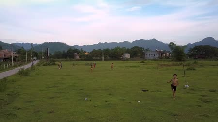 вратарь : PHONG NHAVIETNAM - MAY 10 2018: Flycam shows children playing football on green grass field using self made gate from sticks against mountain range on May 10 in Phong nha