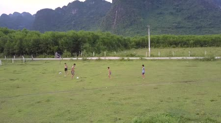 вратарь : PHONG NHAVIETNAM - MAY 10 2018: Children spend time playing football on green grass field along narrow road against high mountains aerial view on May 10 in Phong nha