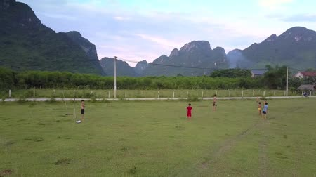 вратарь : PHONG NHAVIETNAM - MAY 10 2018: Flycam films local children playing football on green grass field against high steep mountain ranges on May 10 in Phong nha