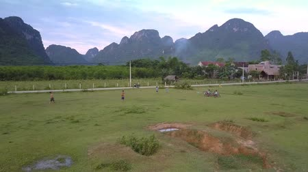 新芽 : PHONG NHAVIETNAM - MAY 10 2018: Flycam shoots active schoolchildren playing football on grass field by tiny village against steep mountain ranges on May 10 in Phong nha 動画素材
