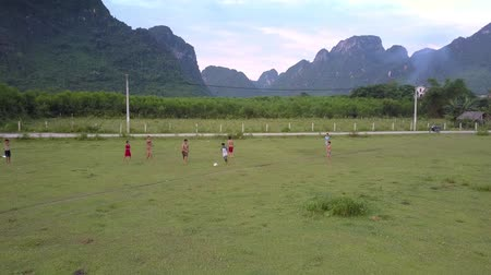 вратарь : PHONG NHAVIETNAM - MAY 10 2018: Local boys play football in green valley along narrow road surrounded by mountains under gray cloudy sky aerial view on May 10 in Phong nha