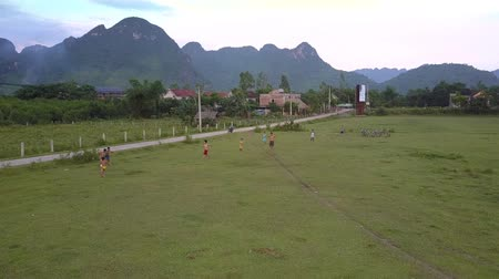 вратарь : PHONG NHAVIETNAM - MAY 10 2018: Active children play football on green flat meadow against little village under gray cloudy sky aerial view on May 10 in Phong nha