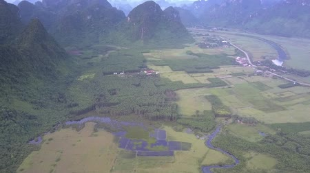accurate : aerial motion above calm green valley and accurate fields near little village and high steep mountain ranges Stock Footage