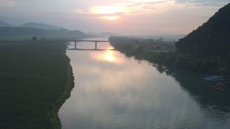plateau : amazing sunset panorama above wide calm tropical river with high narrow bridge near tiny village aerial view