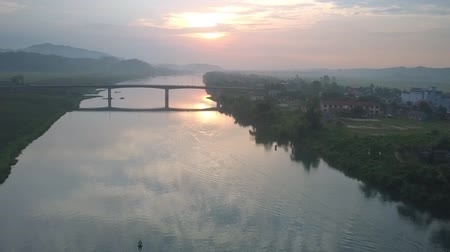 плато : beautiful wide long tropical river under narrow bridge between green highland and small town silhouette at summer sunset Стоковые видеозаписи