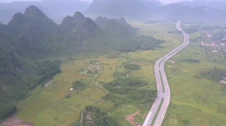 плато : long wide asphalt highway crosses amazing valley with fields and village under grey thick fog bird eye view