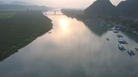 плато : flycam films calm wide river surface with high narrow bridge under cloudy sky with bright pink sunset reflected on water