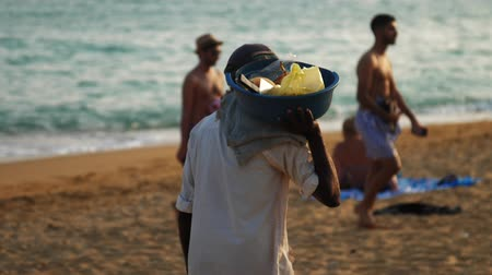 pažba : MIRISASRI LANKA - APRIL 01 2019: Sunburnt local vendor in cap carries on right shoulder blue basin with fruit on beach close backside view slow motion on April 01 in Mirisa