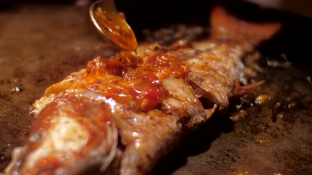 generoso : generously smeared with traditional sweet sauce delicious sea fish lies on pan and fries slow motion close view