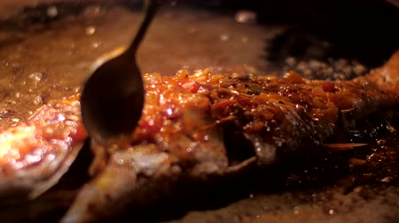 olive oil pour : person pours sweet mango sauce with silver spoon on tender carp fillet frying in olive oil on pan slow motion close view