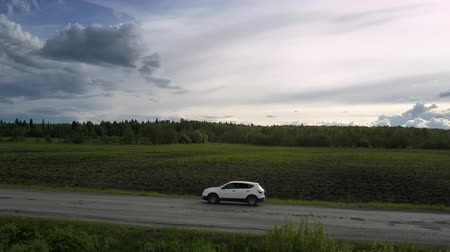 old pit : white sport utility vehicle shakes driving along grey old road under cloudy sky aerial view. Concept road destruction and speed Stock Footage