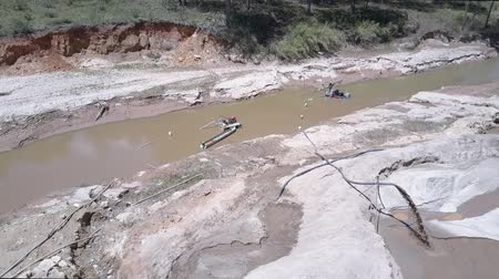pedreira : extraction equipment pumps grit from shallow muddy river and sand flows down through pipe on quarry upper view. Concept aggressive development of nature and illegal sand mining