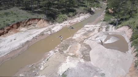dragueur : flycam rises over long pipe pumping fast sand stream into small quarry surrounded by narrow muddy river and green forest.Concept aggressive development of nature and illegal sand mining