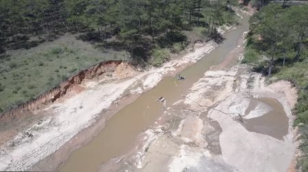 emme : qualified miners work on narrow muddy river and extract grit using special equipment amidst green forest bird eye view. Concept disruption of ecological balance Stok Video