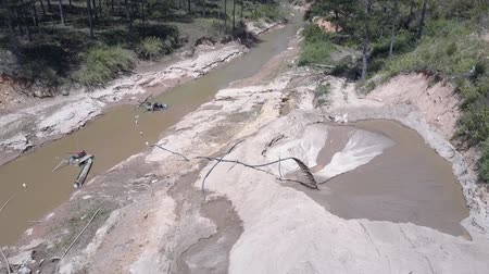 pedreira : flycam films fast sand stream running through long pipe extracting sand from narrow muddy river bottom upper view. Concept riverbed destruction and illegal sand mining