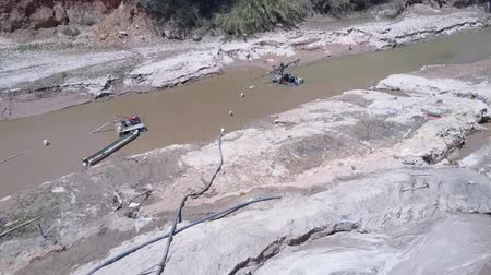 emme : motion to grit miner standing on special equipment pumping wet sand from shallow muddy river bottom upper view. Concept riverbed destruction and illegal sand mining Stok Video