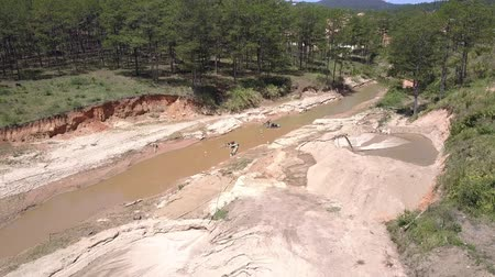 emme : narrow river used for sand extracting works runs in highland passes small quarry and crosses green forest bird eye view. Concept disruption of ecological balance