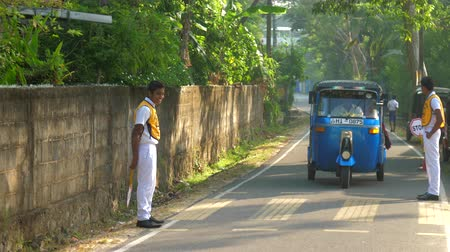 scholar : ColomboSRI LANKA - APRIL 05 2019: Sinhalese schoolboys in white yellow uniform at grey asphalt road with blue transport object slow motion. Concept system of education on April 05 in Colombo Stock Footage