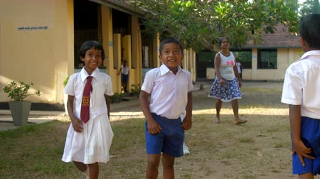 воспитание : ColomboSRI LANKA - APRIL 05 2019: schoolchildren shake hands wandering along schoolyard on first day at school slow motion. Concept system of education on April 05 in Colombo Стоковые видеозаписи