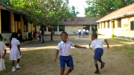 schoolyard : ColomboSRI LANKA - APRIL 05 2019: Funny children play on schoolyard at yellow building against green trees in autumn slow motion. Concept system of education on April 05 in Colombo