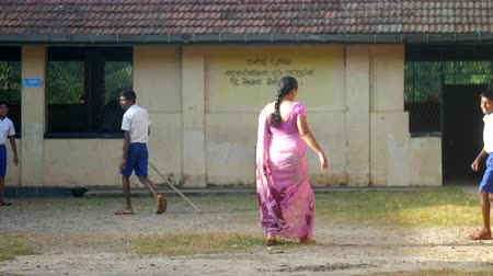 raises : ColomboSRI LANKA - APRIL 05 2019: School teacher in purple dress raises classroom keys from grass against building slow motion backside view. Concept system of education on April 05 in Colombo