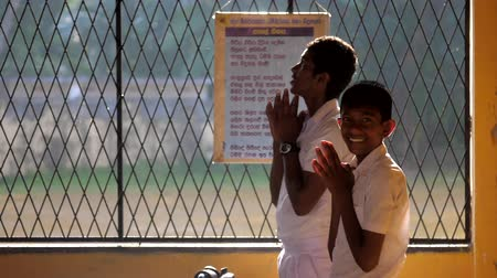 school uniform : ColomboSRI LANKA - APRIL 05 2019: Schoolboys in white uniforms pray standing in yellow classroom with smile slow motion. Concept system of education on April 05 in Colombo