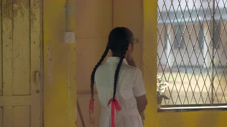 scolari : ColomboSRI LANKA - APRIL 05 2019: Long haired girl prays before lesson standing in classroom at window and pot plant slow motion backside view. Concept system of education on April 05 in Colombo