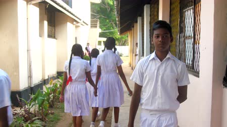 schoolyard : ColomboSRI LANKA - APRIL 05 2019: Sinhalese boys and girls in uniforms walk along thin road between school buildings slow motion. Concept system of education on April 05 in Colombo