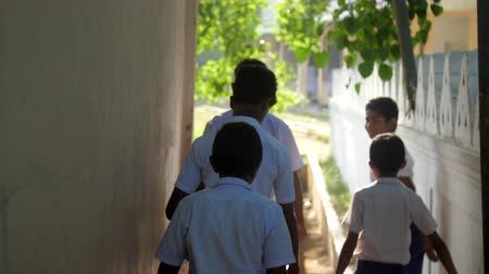 vagabundo : ColomboSRI LANKA - APRIL 05 2019: Schoolboys in uniforms walk from building to schoolyard lit by sun on last school day slow motion backside view. Concept system of education on April 05 in Colombo