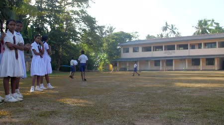 schoolyard : ColomboSRI LANKA - APRIL 05 2019: Sinhalese boys play on schoolyard and girls look against building on sunny autumn day slow motion. Concept sport and competition on April 05 in Colombo Stock Footage